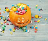 stock photo of jack-o-laterns-jack-o-latern  - Jack o lantern halloween pumpkin filled with multiple colorful sweets and candies over the wooden board background composition - JPG