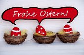 stock photo of sm  - Three Red Dotted And Striped Easter Eggs In Easter Baskets Or Nest On White Wooden Background With Comic Speech Balloon With German Text Frohe Ostern Means Happy Easter Used As Easter Decoration Or Easter Greetings