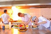 picture of pasta  - Handsome chef dressed in white uniform decorating pasta salad and seafood fish in modern kitchen - JPG
