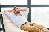 stock photo of adults only  - Handsome young man holding hands behind head while sleeping on the couch - JPG