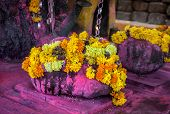 picture of pooja  - Purple stone with Saffron flower garlands in the Hindu temple near Arambol beach Goa India - JPG