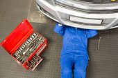 picture of garage  - Mechanic lying and working under car at the repair garage - JPG