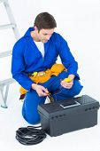 picture of  multimeter  - Handsome electrician using multimeter over white background - JPG