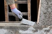 pic of trowel  - Staircase making workers hand with trowel and concrete home renovation - JPG