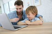 stock photo of daddy  - Daddy and son playing on laptop computer - JPG