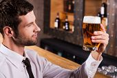 picture of toothless smile  - Side view of handsome young man in shirt and tie examining glass with beer and smiling while sitting at the bar counter - JPG