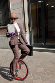 stock photo of unicycle  - woman through the city with the unicycle to go to work - JPG