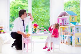 stock photo of baby doll  - Happy family young father and his little daughter cute curly toddler girl wearing a dress playing together with doll house having toy tea party in a white sunny nursery - JPG