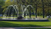 pic of water jet  - Fountain with water jets illuminated by sunlight in a city park - JPG