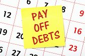 stock photo of debt free  - A reminder to Pay Off Debts on a yellow sticky note attached to the page of a calendar - JPG