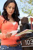 stock photo of mailbox  - Worried Hispanic Woman Checking Mailbox - JPG