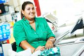 stock photo of cashiers  - Portrait of seller assistant or cashdesk cashier worker teller in supermarket store - JPG