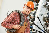 stock photo of electrician  - electrician engineer worker with cable in front of fuseboard equipment - JPG