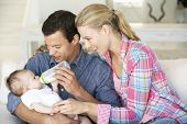 image of feeding  - Young Family With Baby Feeding On Sofa At Home - JPG
