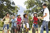 image of safety  - Group Of Children Having Safety Lesson From Adult Whilst Riding Bikes In Countryside - JPG