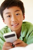 image of pre-teen boy  - Young boy using smartphone - JPG