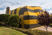 picture of tent  - Brown and yellow striped tent covers a house for fumigation process - JPG