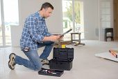 stock photo of kneeling  - Builder kneeling by his toolbox - JPG