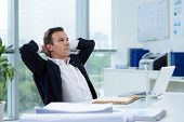 stock photo of daydreaming  - Businessman daydreaming in the office with hands behind his head - JPG
