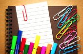 stock photo of marker pen  - Note paper clip on notebook with colorful marker pens and paperclips on brown cardboard background - JPG