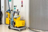 foto of slip hazard  - Yellow mop bucket and set of cleaning equipment in the airport - JPG