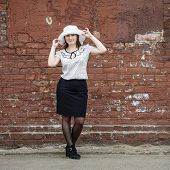 picture of blouse  - Photo of a woman in a white hat blouse and black skirt standing against the backdrop of an old vintage brown brick wall - JPG