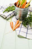 foto of bucket  - Carrots inside metal bucket on the light green wooden table - JPG