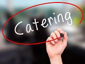 image of catering  - Man Hand writing Catering with marker on transparent wipe board - JPG