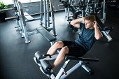 picture of crunch  - Sportsman doing crunches on a bench at the gym - JPG