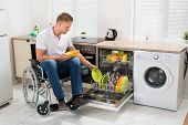 stock photo of blind man  - Young Disabled Man Sitting On Wheelchair Working In Kitchen - JPG