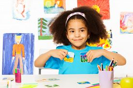 image of child development  - Cute African girl playing developmental game holding cards matching relation by table sitting in playroom with wall behind full of children drawings - JPG