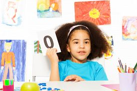 pic of zero  - African girl holds flashcard with zero number at the desk while sitting in playroom with wall behind which is full of kids drawings - JPG