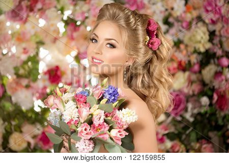 Beautiful fashion model. Sensual bride. Woman with wedding hair and make up. Sweet flowers backgroun