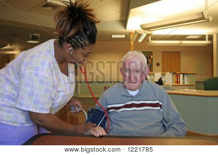 Picture or Photo of Nursing staff checking blood pressure of nursing home resident.