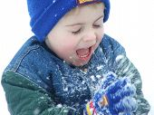 pic of little boy  - a little boys is clapping snow from his gloves onto his face - JPG