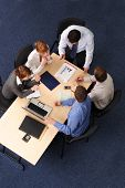 pic of marketing strategy  - Businesspeople gathered around a table for a meeting takling about strategy - JPG