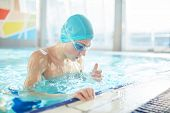 Schoolboy in swimwear and goggles spending leisure in swimming-pool poster