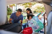 Family Leaving For Vacation Loading Luggage Into Car poster