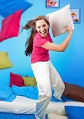 young teenage-woman is making a pillow-fight