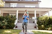 Father Giving Son Ride On Shoulders Outside House poster