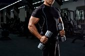 Muscular Bodybuilder Doing Exercises With Dumbbell Over Black Background.strong Athletic Man Shows B poster