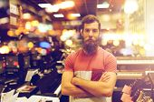 people, musical instruments and small business concept - male assistant or customer with beard at mu poster