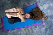 stock photo of hamstring  - Foreshortened view looking down on attractive long haired woman on yoga mat stretching hamstrings in studio against a mottled background - JPG