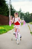 pic of bagpack  - Young school girl with bagpack rides her pink bike to school - JPG