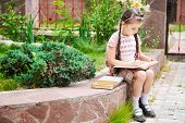 foto of bagpack  - Young school girl with pink bagpack sits reading the book - JPG