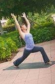 image of virabhadrasana  - an athletic brown haired woman is doing yoga exercise Virabhadrasana or warrior 1 pose outside on a sidewalk in public on an overcast morning. ** Note: Slight graininess, best at smaller sizes - JPG