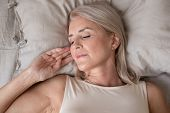 Peaceful Beautiful Mature Woman Sleeping In Bed Close Up poster