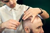 Cropped Of Male Young Hairdresser Barber Making Short Haircut For His Client In Modern Barbershop. C poster