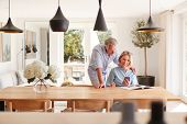 Senior Couple Relaxing With Magazine At Home Looking At Mobile Phone Sitting At Dining Room Table poster