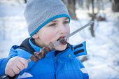 In Winter, In The Forest, The Boy Eats Kebab, Meat On A Skewer. He Is Very Hungry. poster